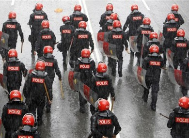 Malaysian riot police officers march on a street under heavy rain during a rally in Kuala Lumpur, Malaysia, Saturday, July 9, 2011.