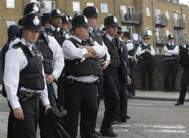 British police officers stand on duty during the children day of Notting Hill Carnival in London, Sunday, Aug. 28, 2011.