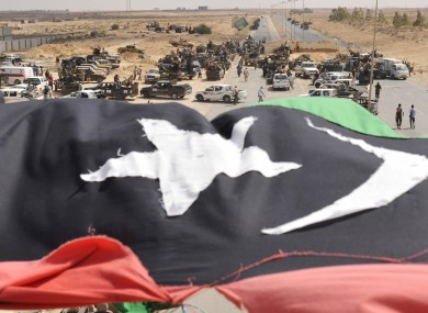 Libyan revolutionary fighters are seen behind the country's new flag while gathering on the main road outside Sirte yesterday.