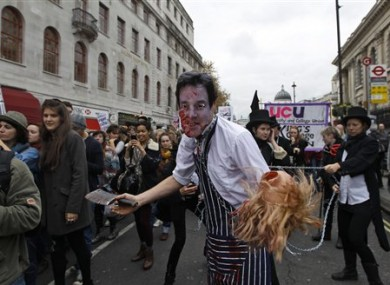 A students waring a mask depicting British Deputy Prime Minister Nick Clegg, pretends to be a butcher, during an anti-cuts student protest in central London, Wednesday, Nov. 9, 2011.