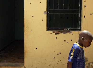 A boy looks at bullet holes in the compound where the two hostages were held in Sokoto, Nigeria.