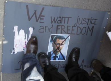 Protesters stand on a crossed picture of Syrian President Bashar Assad during a rally against his regime in front of the Syrian embassy in Belgrade.