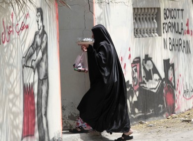 A woman in Barbar, Bahrain enters a house, where the outer walls are spayed with anti Grand Prix graffiti