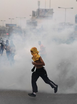 Anti-government protesters run through tear gas fired by riot police Friday, April 20, 2012