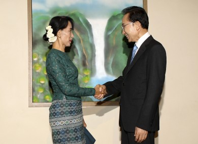 South Korean President Lee Myung-bak, right, shakes hands with Burma's opposition leader Aung San Suu Kyi