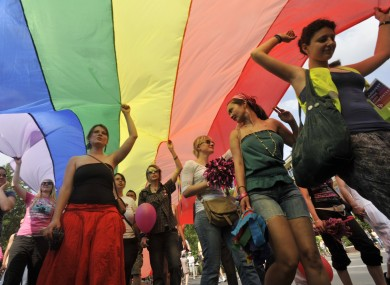 Gay right activists march with a rainbow flag during the Gay Pride parade in downtown Budapest, Hungary, Saturday, June 18, 2011