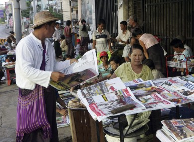 A man buys a weekly news journal at a roadside newspaper stand in Yangon. Only state-sponsored titles are allowed to publish daily - a regime that will end from tomorrow.