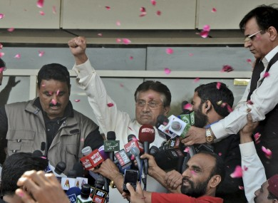 Musharraf, centre, gestures to his supporters, unseen, upon his arrival to Karachi airport