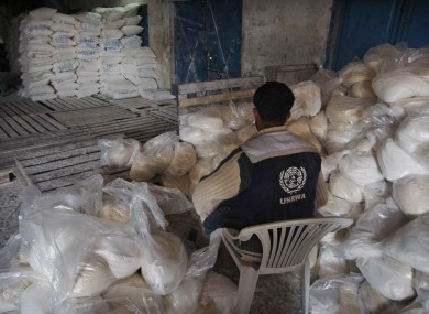A Palestinian worker sits next to food aid at a United Nations distribution centre in Gaza City (file photo).