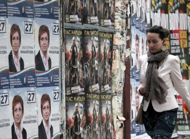 A woman passes by election campaign posters in Sofia