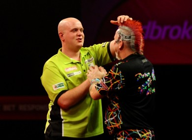 Michael Van Gerwen consoles Peter Wright after winning the Final of The Ladbrokes World Darts Championship at Alexandra Palace, London.