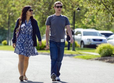 Mark Zuckerberg, president and CEO of Facebook, walks with Priscilla Chan