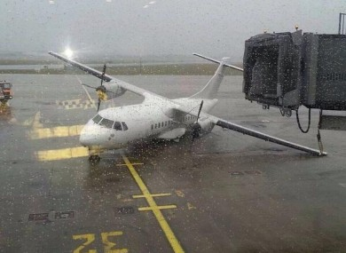 A stationary plane knocked over amid the high winds.