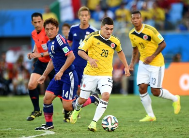 Japan's Toshihiro Aoyama battles for the ball with Colombia's Juan Quinero.